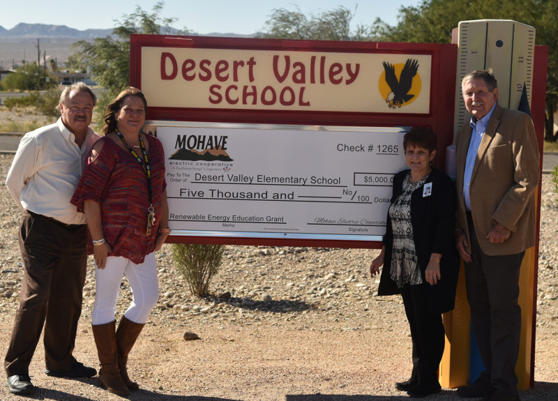 Several people standing next to the Desert Valley School sign, with a big $5,000 check.