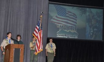 Boy Scouts holding the American flag, in front of a projection screen.