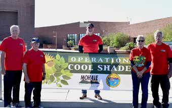 Several people standing in front of building holding a large Operation Cool Shade banner