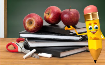 A smiley face pencil illustration pointing to a stack of book and binders on a desk in front of a chalkboard, with apples piled on top.