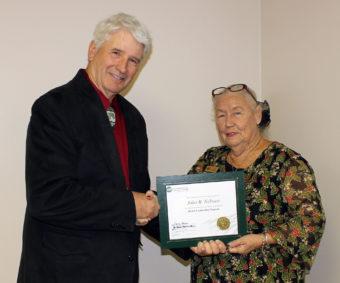Mohave Electric Cooperative Board of Directors Lyn Opalka, presents the accredited NRECA Board Leadership Certificate to John Nelssen.