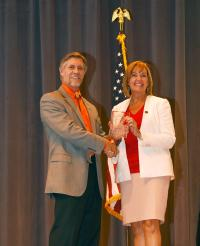 Tyler Carlson presenting Regina Cobb an award on a stage.