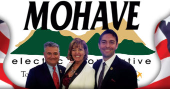 Sonny Borrelli, Regina Cobb, and Leo Biasiucci standing in front of Mohave Electric Cooperative flag