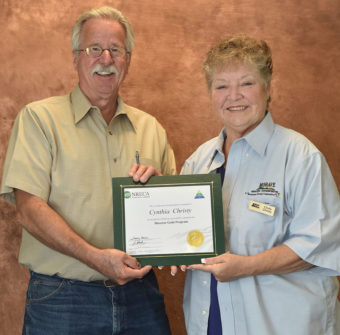 Board of Directors President Joe Anderson presents the Gold Director Certificate to fellow Director Cindy Christy.