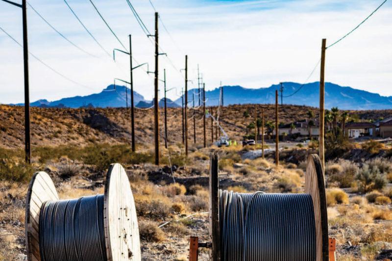 fiber spools in desert next to powerpoles