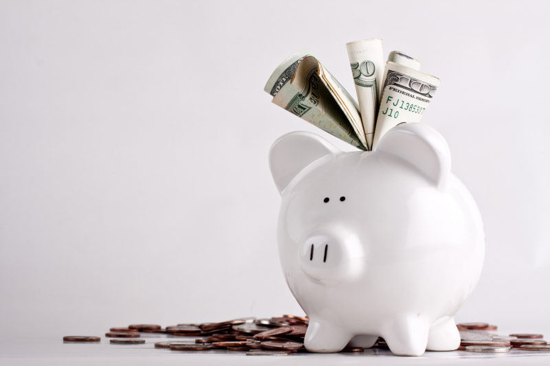 piggy bank with money sticking out of the top