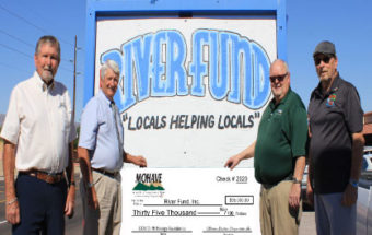 """Several men standing next to a River Fund """"Locals helping locals"""" sign, holding a big $35,000 check."""